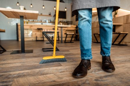 Sweeping a hardwood floor with a broom
