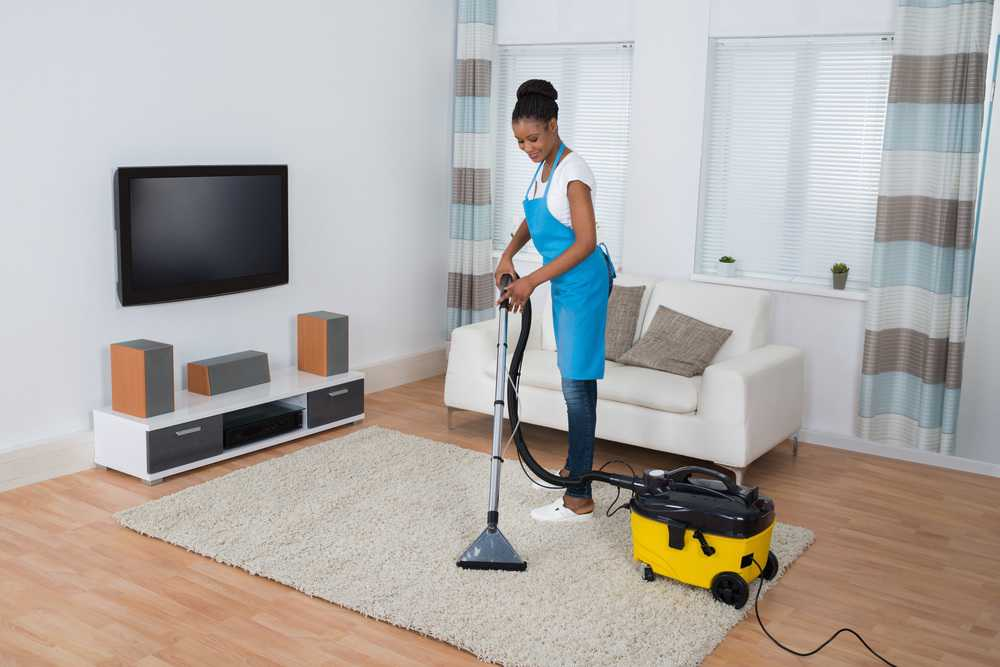 Woman cleaning the living room floor with a professiona vacuum