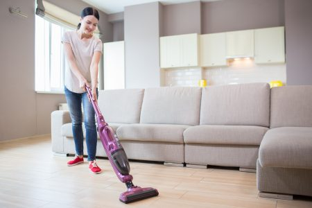 Woman cleaning hard floor with a cordless stick vacuum