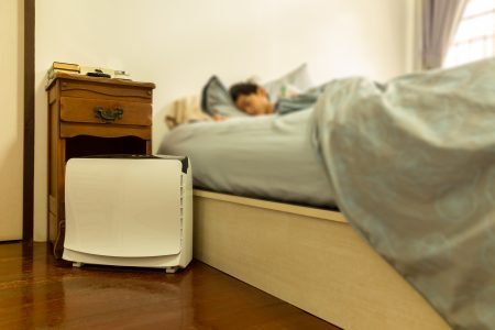 Person sleeping with an air purifier