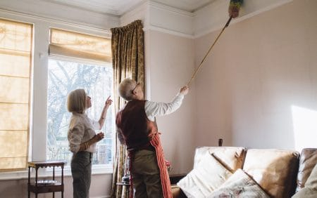Husband and wife dusting the ceiling