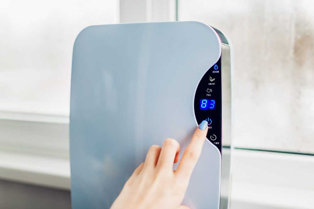 Woman turning on dehumidifier