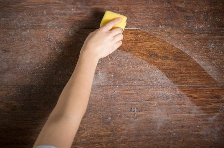 Woman cleaning dusty wood floor
