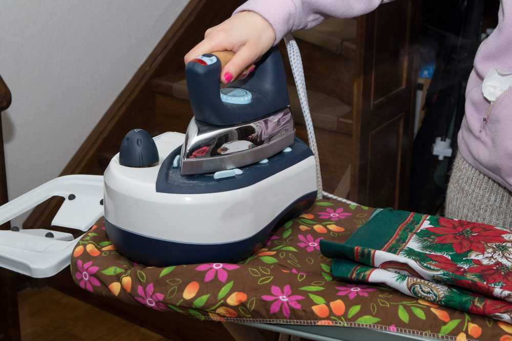 Woman ironing with a steam generator iron
