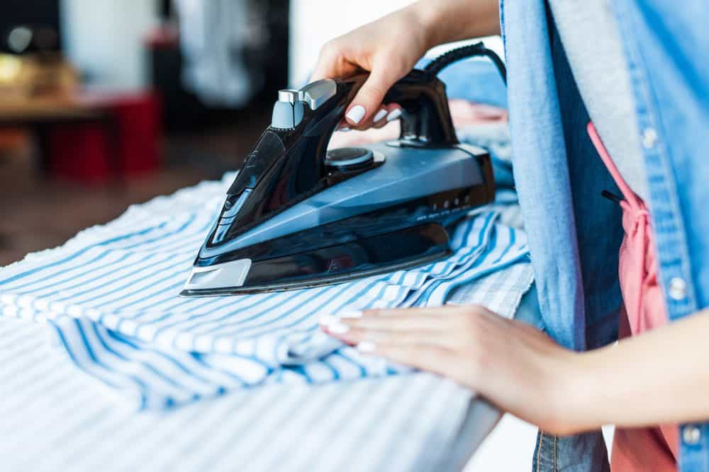 Woman ironing a shirt with a dry iron