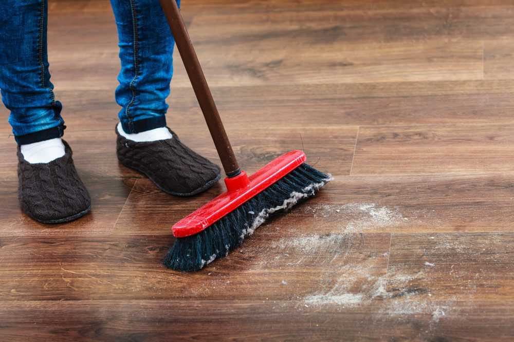Cleaning woman sweeping wooden floor with push broom