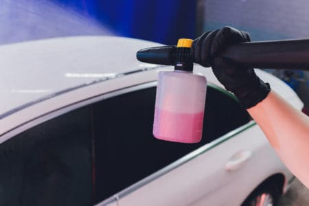 gloved hand cleaning the car using pressure washer with pink detergent