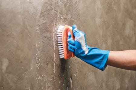 Cleaning the concrete wall with soap solution