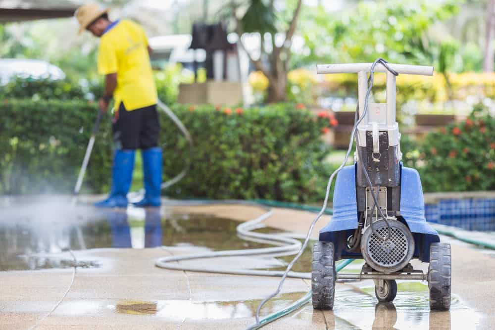 Man cleaning pool tiles with pressure washer