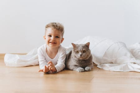 Cute toddler lying on the floor with pet cat