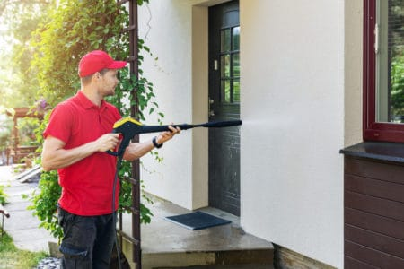 Man with high pressure washer cleaning house facade